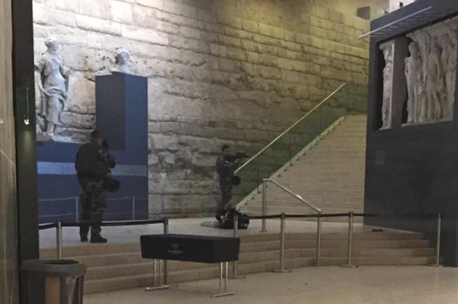 Deux soldats gardent un homme au sol après l'attaque d'un militaire à la machette au Carroussel du Louvre à Paris le 3 février.