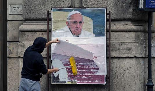 Un employé de la ville de Rome recouvre une des affiches critiquant le pape François, le 5 février.