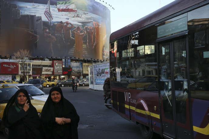 A Téhéran, le 30janvier, deux Iraniennes devant une fresque qui évoque l'arrestation, en janvier 2016, de marines américains par les Gardiens de la révolution.