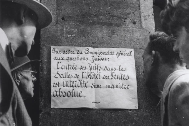 Des hommes regardant une affiche à l'entrée de l'hôtel des ventes Drouot : «Par ordre du Commissariat général aux questions juives, l'entrée des juifs dans les salles de l'hôtel des ventes est interdite de manière absolue.»