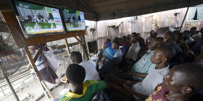 Le 31 mars 2015, des Nigérians regardent à la télévison les résultats de la présidentielle, à Lagos.