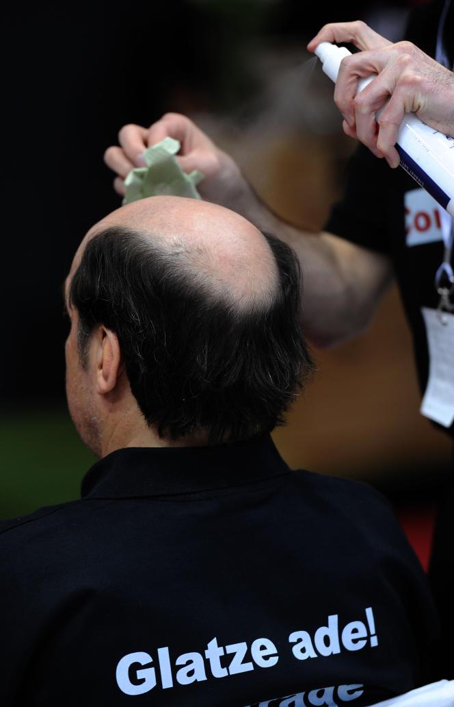 Un coiffeur prépare le crâne d'un client chauve avant la pose d'une perruque, au Salon Beauty et Top Hair de Düsseldorf, en 2011.