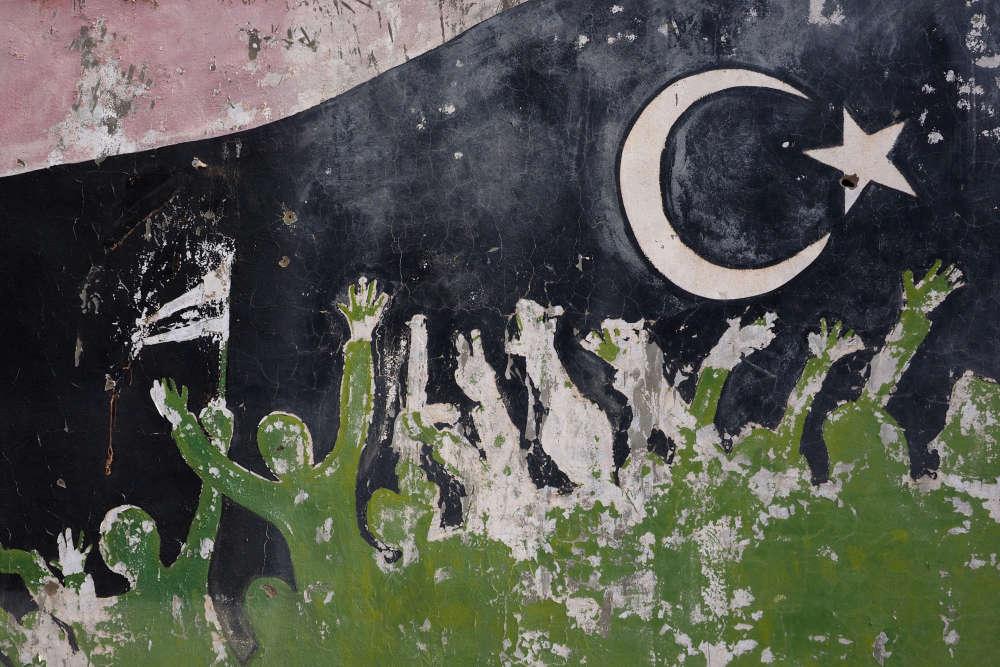 Dans le Musée de la révolution, désespérément vide, une fresque rappelle la révolte du peuple libyen, les bras levés.