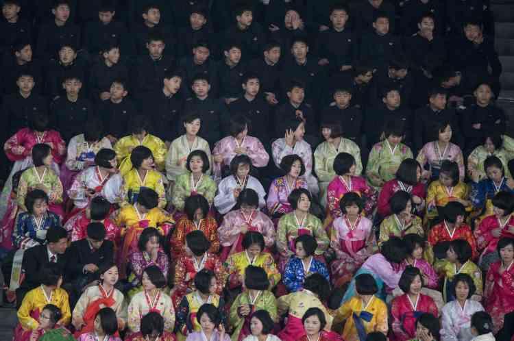 Des fonctionnaires nord-coréens en uniforme sombre et des femmes en robe traditionnelle aux couleurs vives regardent le spectacle.