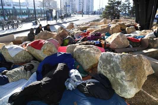 Un migrant allongé entre les blocs de pierre sous un pont du boulevard Ney, à Paris, le 15 février 2017.