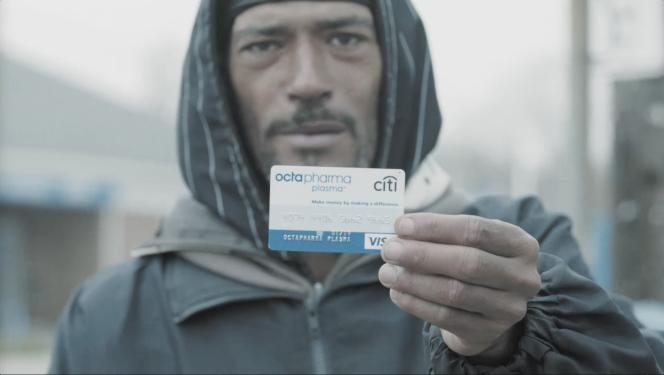 Un donneur de plasma montrant la carte sur laquelle lui sont versés ses 60 dollars par semaine, à la sortie du centre Octapharma de Lorain Avenue, Cleveland, en mai 2016.