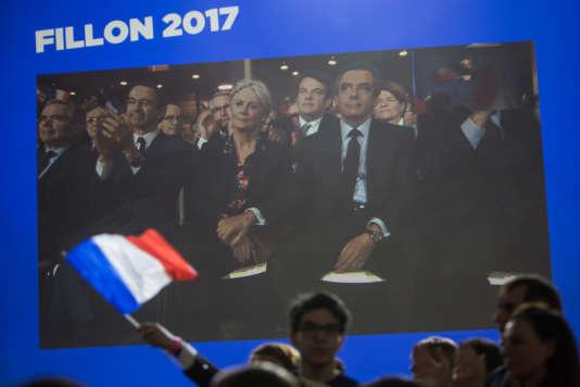 Sur l'écran installé derrière la scène, François Fillon prend la main de son épouse Penelope lors du meeting du 29 janvier à Paris.