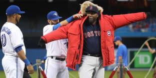 Lors d'un match de base-ball, David Ortiz, des Boston Red Sox, reçoit deux doudounes Canada Goose en cadeau du joueur Joe Bautista des Blue Jays de Toronto.