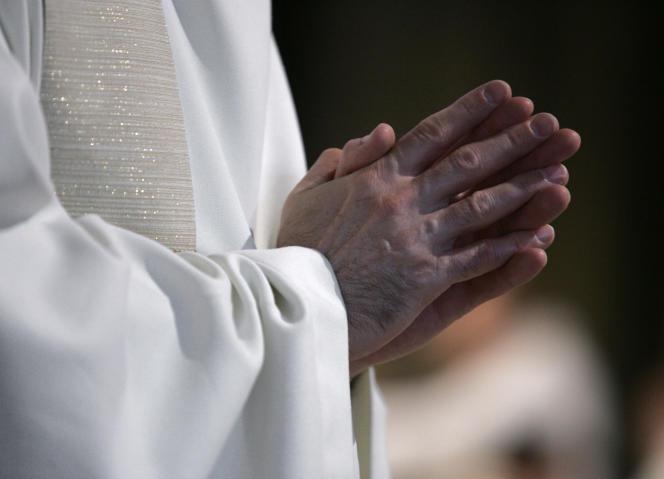 Un prêtre prie les mains jointes, le 24 juin 2006 à la cathédrale Notre-Dame de Paris, lors de la cérémonie d'ordination huit prêtres présidée par Mgr André Vingt-Trois, archevêque de Paris.