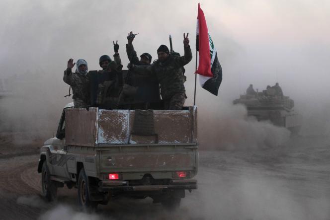 Les forces irakiennes font le V de la victoire alors que démarre l'offensive pour reprendre l'ouest de Mossoul toujours aux mains de l'organisation Etat islamique, le 19 février.