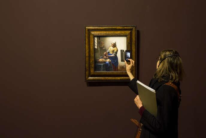 Une visiteuse photographie un tableau de Vermeer avec son téléphone portable au musée du Louvre.