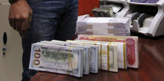 Un homme compte des liasses de dollars américains, à Baghdad, le 21 décembre 2015.