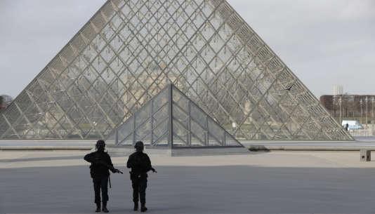 Des policiers à proximité de la pyramide du Louvre.