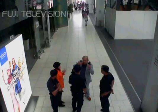 Une image tirée d'une caméra de surveillance montre un homme supposé être Kim Jong-nam, discutant avec un agent de sécurité, après avoir été accosté par une femme à l'aéroport international de Kuala Lumpur, en Malaisie.