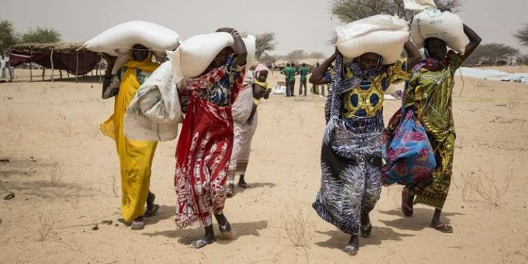 Des femmes transportent des sacs de céréales distribués par le programme alimentaire mondial (PAM) dans le camp de réfugiés de Melia au Tchad, en mars 2016.