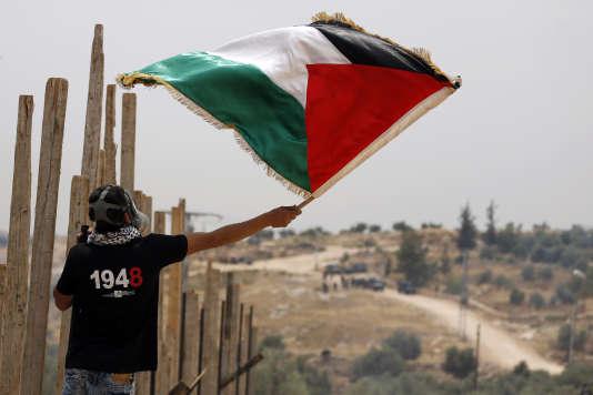 Un jeune homme agite le drapeau palestinien devant les forces de sécurité israéliennes en Cisjordanie, le 13 mai 2016.