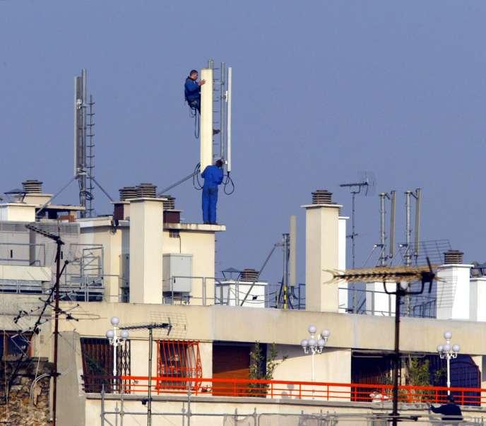 Des techniciens installent des relais téléphoniques sur le toit d'un immeuble parisien, le 20 mars 2003.