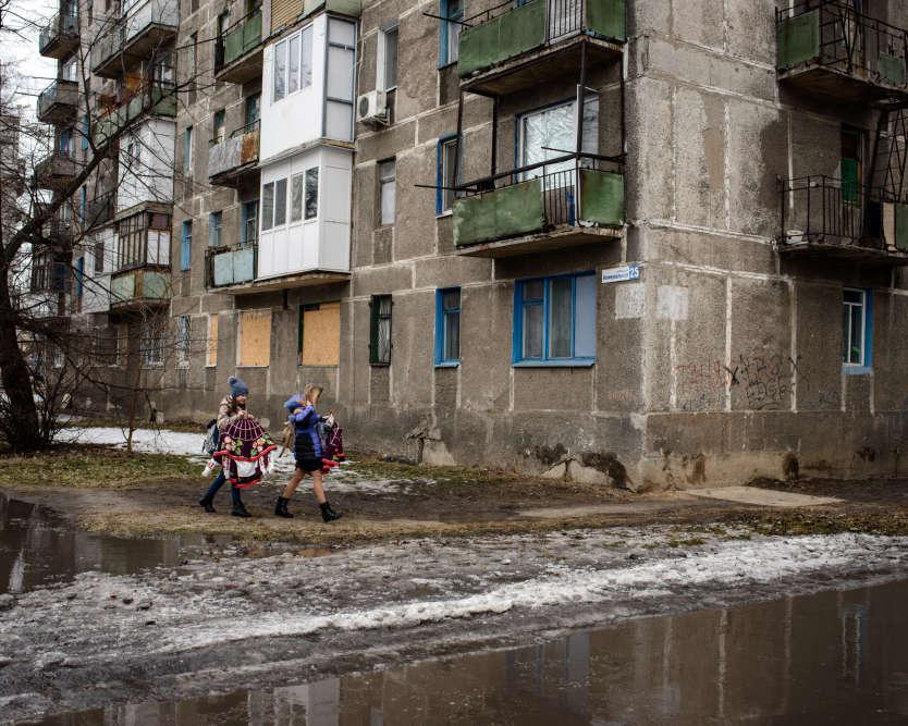Deux collégiennes marchent dans la rue du centre ville, des costumes traditionnels ukrainiens à la main.