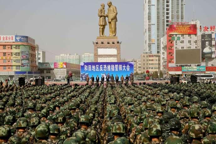 Des policiers militaires chinois prêtent serment contre le terrorisme, à Khotan, au Xinjiang, le 27 février, devant une statue de Mao Zedong et Kurban Tulum, une figure ouïgoure communiste.