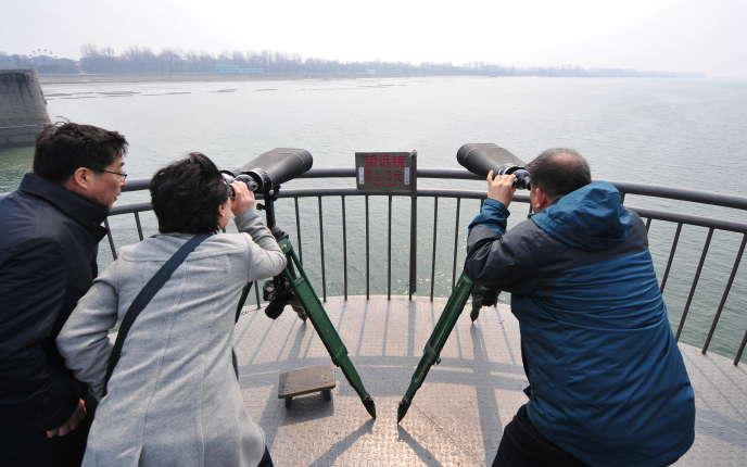 Des visiteurs scrutent la Corée du Nord, en 2009, depuis la ville frontalière chinoise de Dandong, où sont installées des sociétés écrans nord-coréennes selon l'ONU.