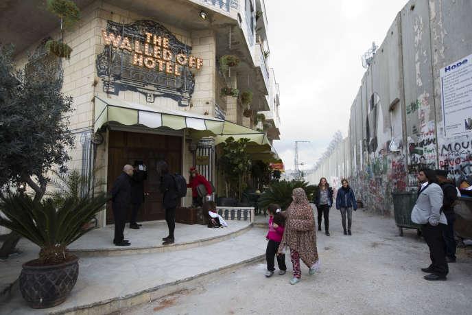 Des habitants passent devant l'hôtel « Walled Off» et le mur de séparation à Bethléem, en Cisjordanie, le 3 mars 2017.