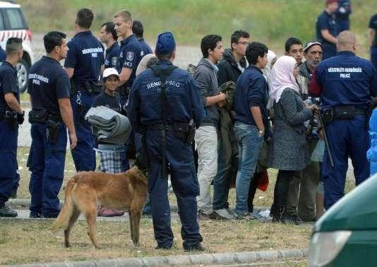 Des demandeurs d'asile attendent d'embarquer dans un bus qui, de Röszke, village sis à la frontière entre la Hongrie et la Serbie, doit les transporter jusqu'à un nouveau camp de migrants, le 25juin 2015.