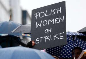 Une femme tient une pancarte lors d'une manifestation pour defendre le droit à l'avortement près des bâtiments abritants les institutions de l'Union européenne, à Bruxelles, en Belgique.