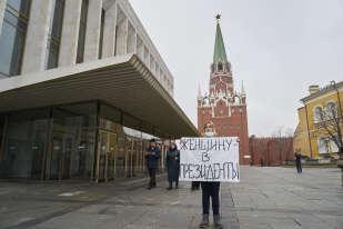 Une militante tient une affiche où est écrit « Une femme pour président!» Lors d'une manifestation à l'intérieur du Kremlin, à Moscou, en Russie, au cours de laquelle des femmes ont été arrêtées.