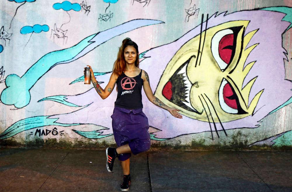 L'artiste Mado, 34 ans, pose devant une de ses peintures sur un mur du quartier de Vila Madalena à Sao Paulo, au Brésil, le 23 février 2017 : «Une entreprise n'a pas voulu m'embaucher pour réaliser une peinture murale sous prétexte que je ne pouvais pas porter le matériel nécessaire, comme les échelles...»