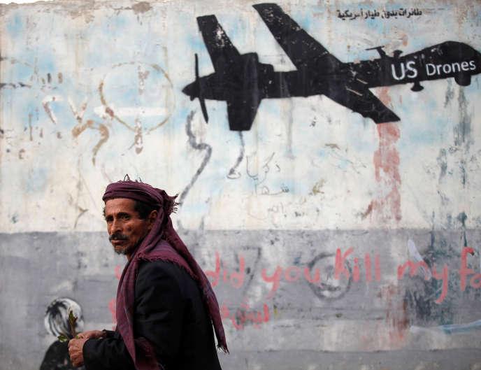 Un homme passe devant un mur de Sanaa, la capitale du Yémen, sur lequel est inscrit un graffiti dénonçant les frappes de drones américains, le 6 février 2017.