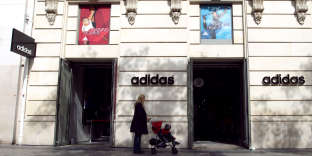A woman walks past the frontage of an Adidas store on the Champs-Elysees Avenue in Paris, on September 25, 2010. AFP PHOTO / THOMAS COEX / AFP PHOTO / THOMAS COEX