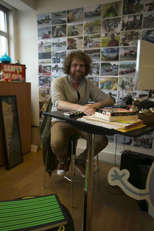 Tommy François à son bureau - hauteur comptoir - devant ses différents reportages pour Ubisoft.