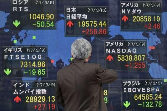 Un passant regarde un tableau de cotations de la Bourse de Tokyo, dans la capitale nippone, le 10 mars 2017.
