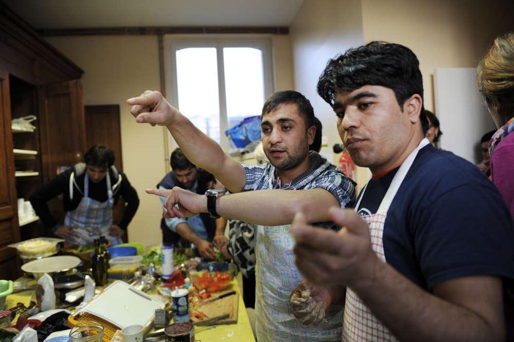 Ahmad dirige les opérations avec Mohammed Agha. A l'initiative du Collectif de Serquigny, commune de l'Eure qui a accueilli prés de trente réfugiés en novembre 2016, dejeunes Afghans préparent des plats traditionnels avec les habitants. Dans la salle des fêtes de Fontaine-l'Abbé, une commune voisine, le 25 février.