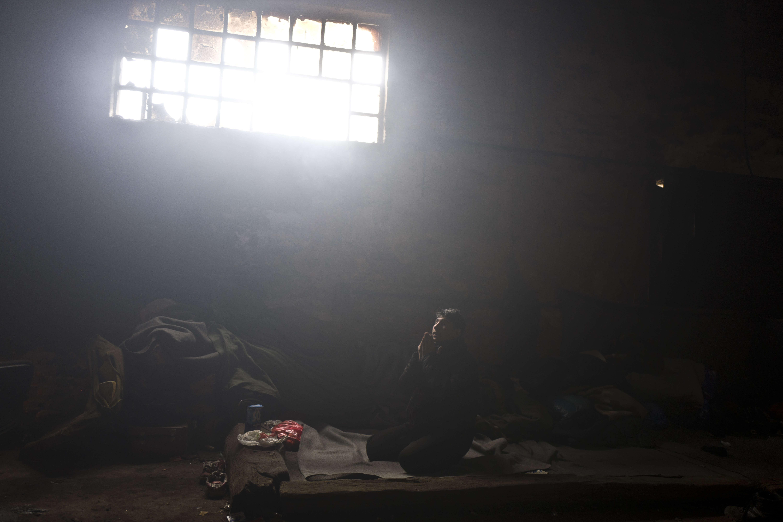 Caesar, 16 ans originaire du Pakistan fait sa prière dans une chambre improsivée.