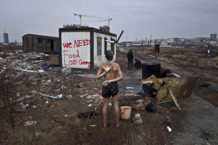 Un migrant de 14 ans se douche à l'extérieur malgré le froid, à côté d'un vieux wagon de train où ils ont passé la nuit.