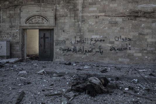 Devant l'Eglise Oum Al-Maouna de Mossoul Ouest,en Irak, le 8 mars 2017. Le corps d'un combattant de l'EI et l'inscription «Interdit d'entrer par ordre de l'Etat Islamique»signée «Hisba», la police de l'EI. La photo est tirée d'un reportage deLaurent Van der Stockt pour Le Monde.