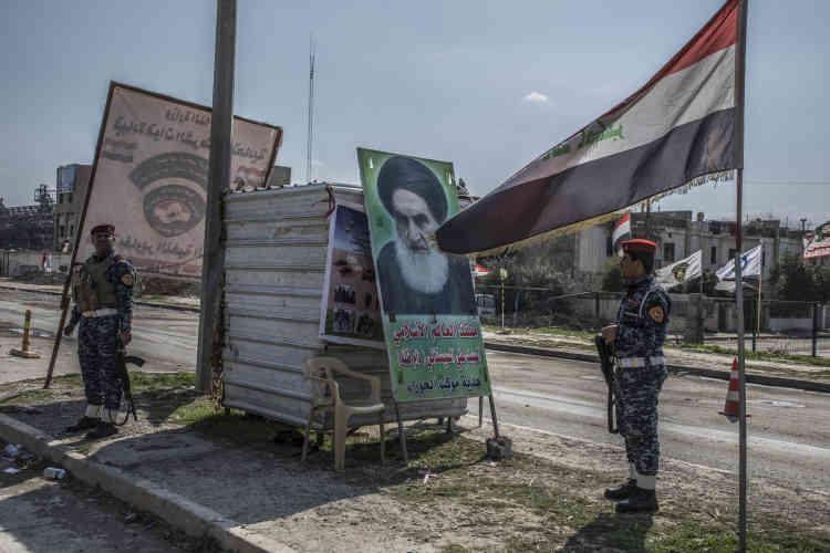 Un check-point de la police fédérale à l'entrée de la partie libérée de Mossoul-Ouest, flanqué d'un drapeau irakien et d'un portrait de l'ayatollah Sistani, leader spirituel des chiites, le 8 mars.