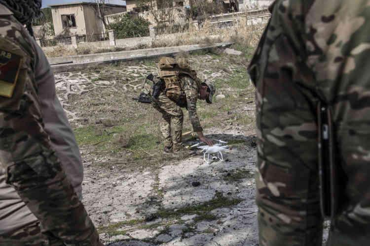 Des membres des divisions de réaction d'urgence opèrent une reconnaissance par drone dans les quartiers repris à l'EI, le 8 mars.