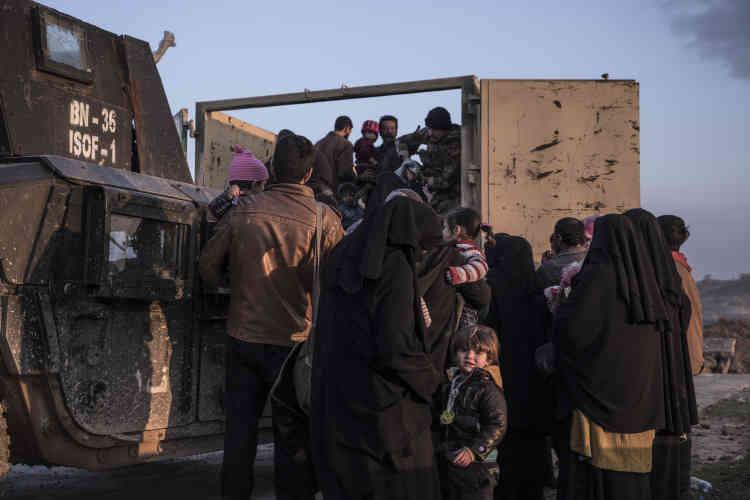 Des habitants de Mossoul-Ouest fuyant les combats sont embarqués par un camion des Forces d'opérations spéciales irakiennes, le 8 mars.