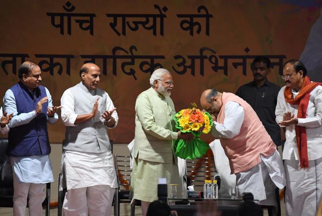 Le premier ministre indien Narendra Modi reçoit des fleurs du président du Bharatiya Janata Party,Amit Shah, le 12 mars à New Delhi.