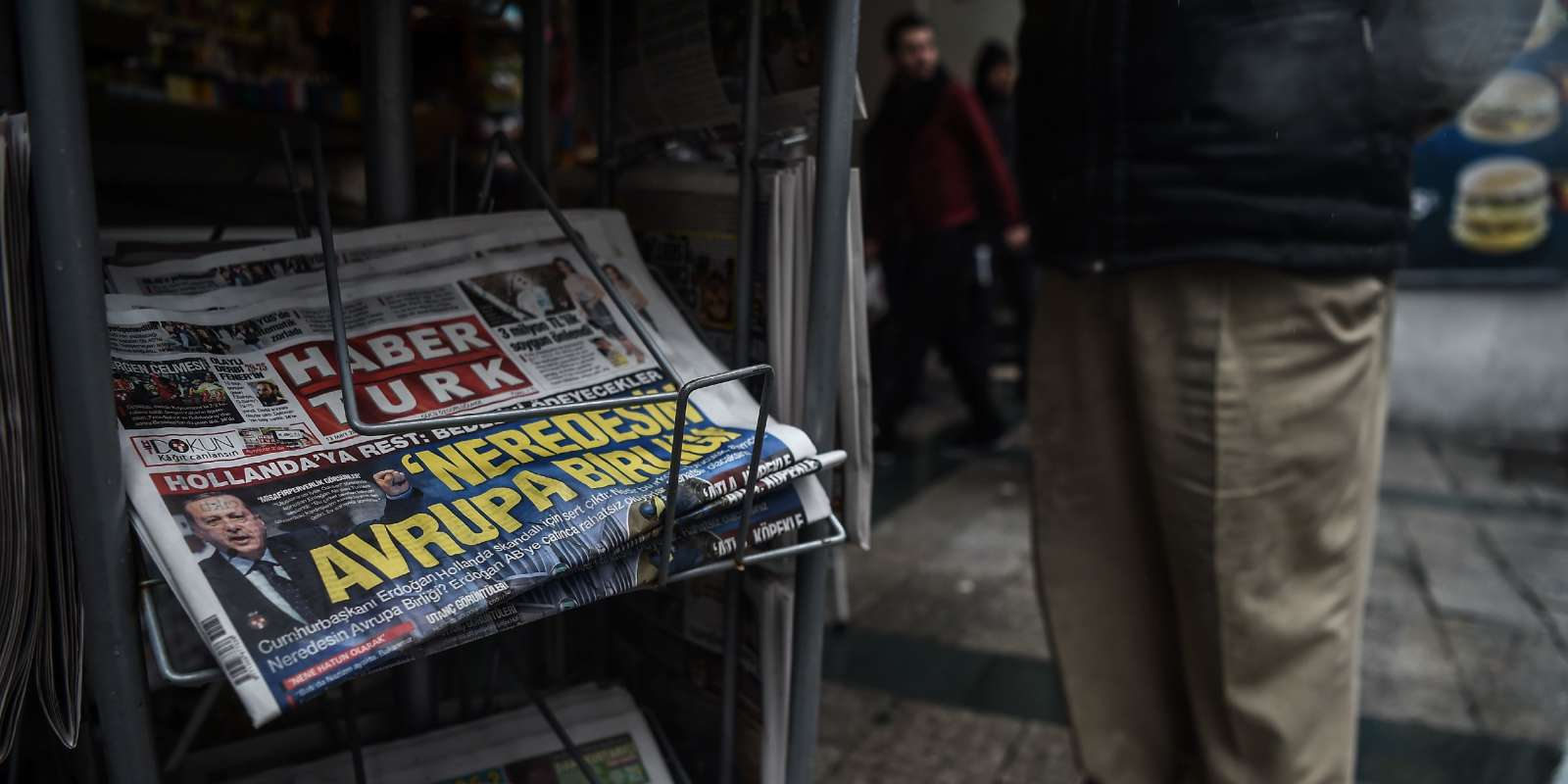 A man looks at a newspaper stand showing their front pages bearing headlines concerning diplomatic tensions between Turkey and The Netherlands, on display in Istanbul on March 13, 2017. Turkish President Recep Tayyip Erdogan warned the Netherlands would pay for blocking his ministers from holding rallies to win support in a referendum on expanding his powers, as a crisis escalated with Turkey's key EU partners.Erdogan also repeated hugely controversial accusations that the Netherlands -- occupied by Nazi Germany in World War II -- was behaving like fascists in its treatment of Turkish ministers. / AFP / OZAN KOSE
