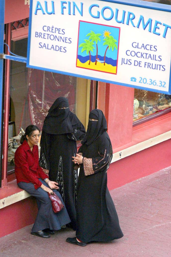 Des femmes Réunionnaises voilées de confession musulmane, discutent le 26 janvier 2004 devant une crêperie bretonne dans une rue du centre de Saint-Denis-de-la-Réunion, où la majorité des commerces sont tenus par des Réunionnais de confession musulmane. AFP PHOTO RICHARD BOUHET / AFP PHOTO / RICHARD BOUHET