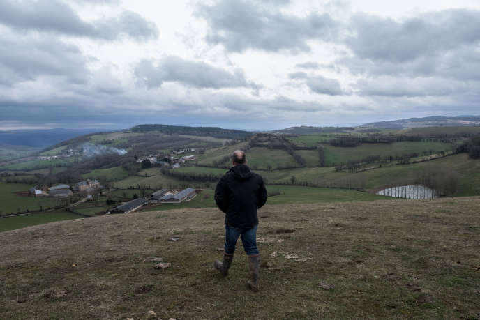 Henry Peyrac marche sur une coline de son exploitation bio familiale, près de Cruéjouls en Aveyron, en mars.