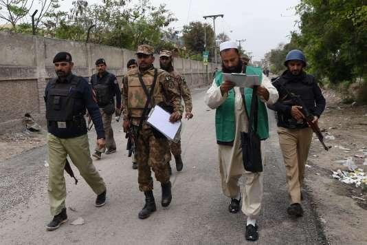 Des soldats et des policiers protègent un responsable du Bureau pakistanais des statistiques (deuxième à partir de la droite) à leur arrivée dans une zone résidentielle de Peshawar (nord-ouest), où ils doivent procéder au recensement, le 15mars 2017.