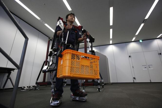 Un employé d'ActiveLink Co., fondé par Panasonic Corp, fait la démonstration du PowerLoader light PLL-011E à Tokyo, le 2juin 2014. Le PowerLoader est un exosquelette robotisé pour aider les agriculteurs et les travailleurs du BTP..