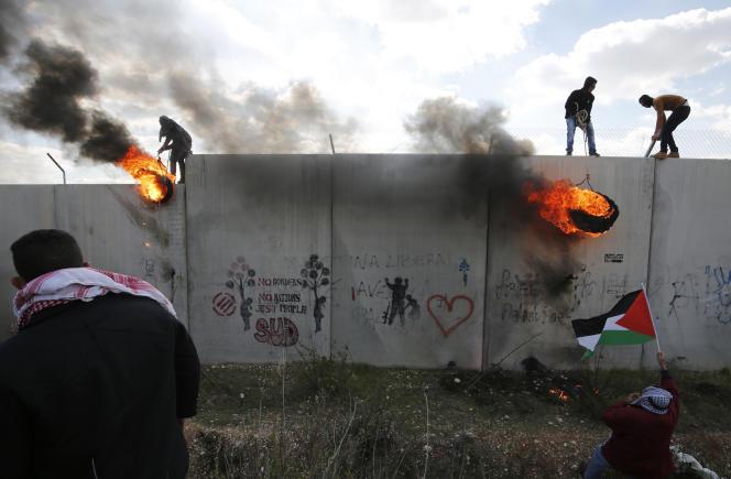 Des Palestiniens manifestent contre les colonies, sur le mur de séparation construit par Israël, à Bilin, près de Ramallah, le 17 février 2017.