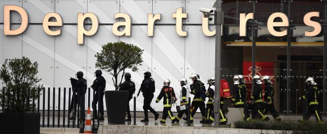 Des policiers et des pompiers progressent dans l'aéroport d'Orly, le 18 mars.