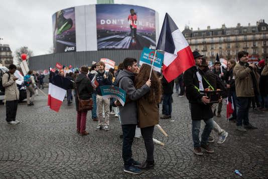 Devant la Bastille deux jeunes militants s'embrassent.
