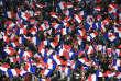 Des drapeaux français brandis par des supporteurs lors d'un match de qualification de la Coupe du monde de football le 11 novembre 2016 entre la France et la Suède au stade de France à Saint-Denis